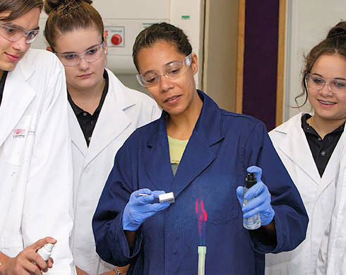 Students watching an experiment by a lecturer