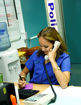 Young woman taking a call in a Police office during the 2000s