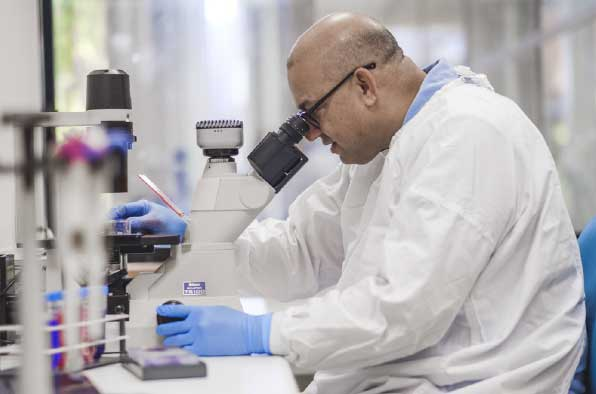 Man in lab coat looking in a microscope