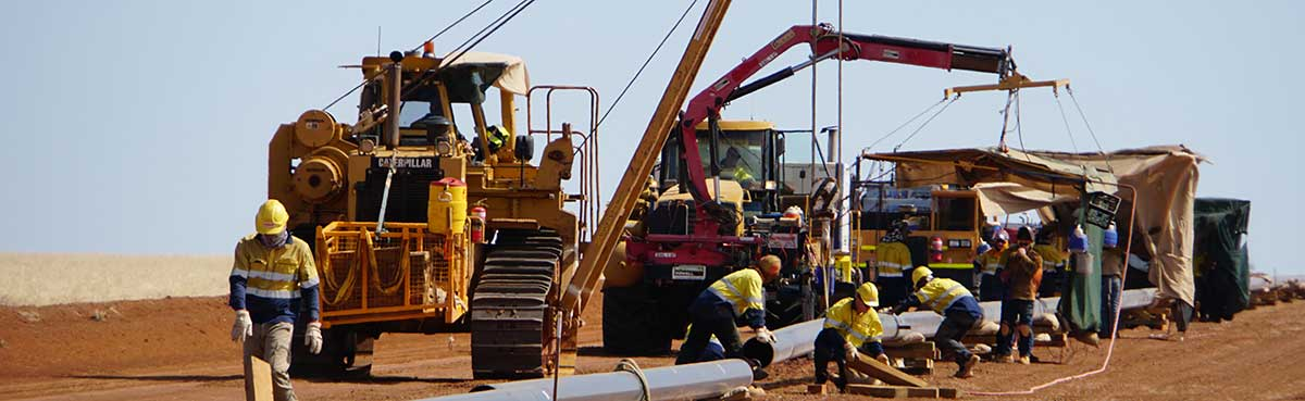 Men and machinery working on a pipeline