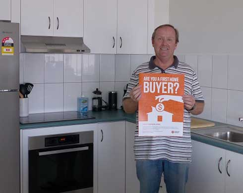 Man standing in kitchen with First Home Buyer factsheet