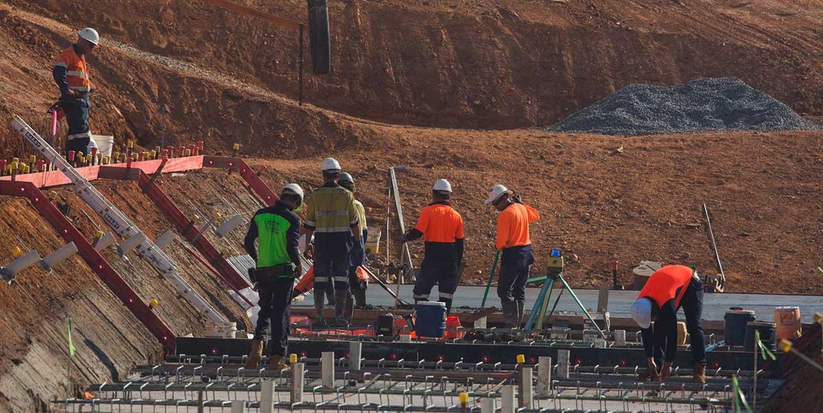 Workmen constructing a concrete pad